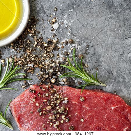 Raw beef steak with peppercorns, sea salt, olive oil and rosemary, over dark slate.  Overhead view.