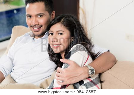 Asian couple cuddling on sofa in living room