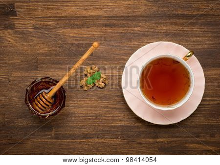 Herbal tea with honey and nuts on wooden background top view.