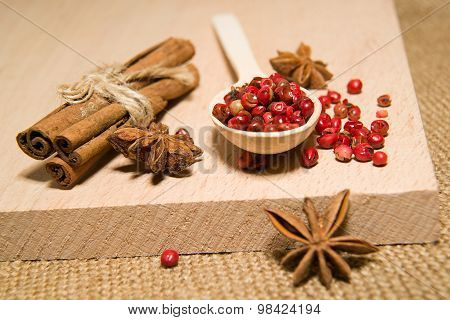 Spoon, Grains Of Pepper, Cinnamon And Star Anis On A Wooden Surface