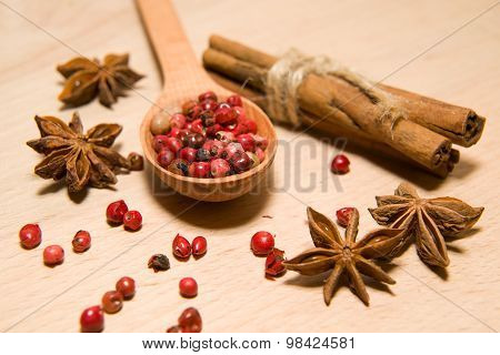 Spoon, Grains Of Pepper, Cinnamon And Star Anise On A Wooden Surface