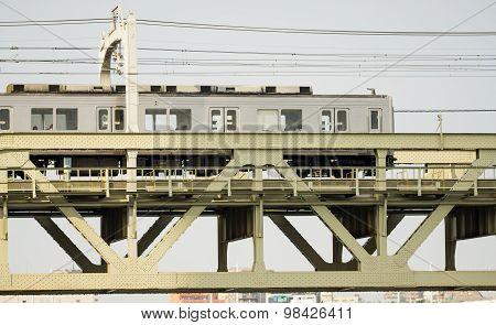 Side view of train over iron bridge