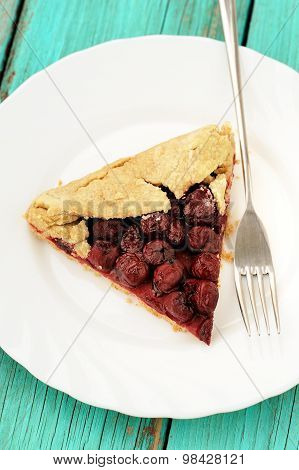 Homemade Vegan Wholegrain Galette With Wild Cherries With Fork In White Plate On Turquoise Table
