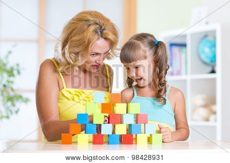 Middle aged mother helping her preschooler daughter build  tower from colorful building blocks as th