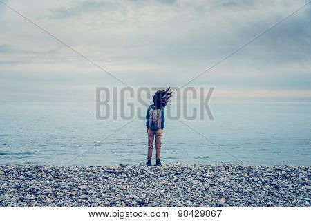 Hiker Girl Standing On Coast In Windy Weather