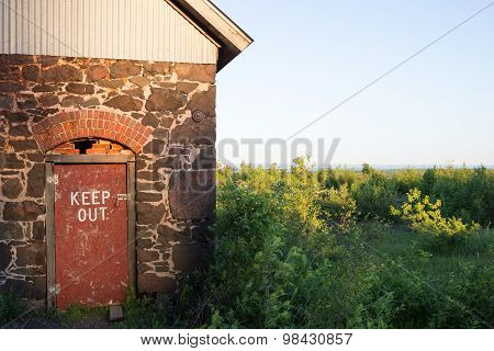 Keep Out Sign Stenciled On Rustic Red Door