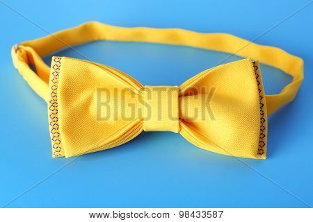 Yellow bow-tie with National emblem of Ukraine on blue background