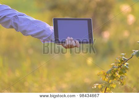 Tablet Computer In  Children's Hand On Nature