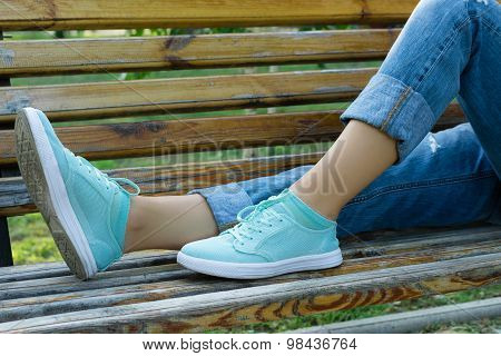 Female Feet In Jeans And Sports Shoes On A Bench Close-up