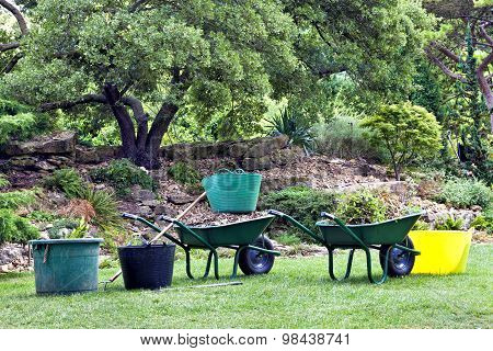 Garden tools green barrows buckets in garden with trees shrubs and rocks