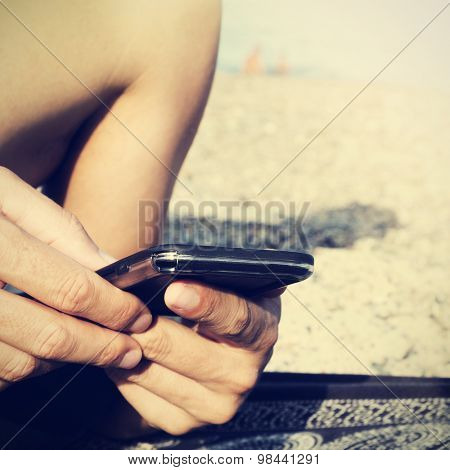 closeup of a young caucasian man using a smartphone on the beach, with a filter effect