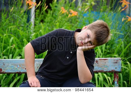 Teenage Boy Sitting On A Bench