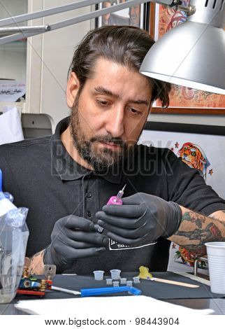 Tattoo artist preparing his ink machine gun before get start working.