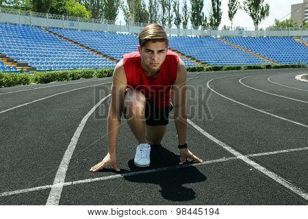 Runner in start position on stadium