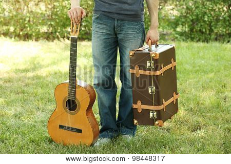 Young man with vintage suitcase and guitar outdoors