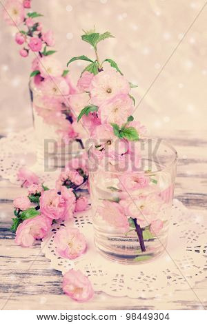Beautiful fruit blossom in glasses on table on light background