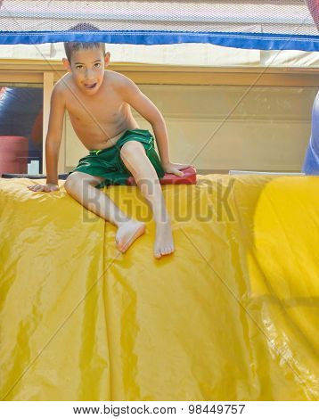 Boy Enjoying A Wet Inflatable Slide