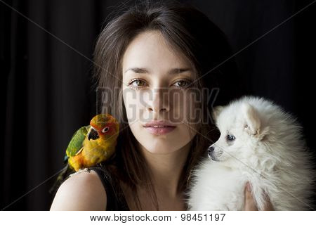 Woman with sun conure on her shoulder and holding a puppy