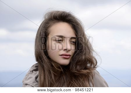 Brunette woman with no makeup on calmly gazing away from the camera.