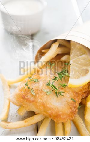 Fish and chips. Fried fish fillet with french fries wrapped by paper cone, on wooden background. Fresh cooked with hot steams.