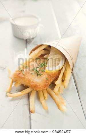 Fish and chips. Fried fish fillet with french fries wrapped by paper cone, on bright wooden background. Fresh cooked with hot smoke.