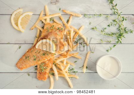 Fish and chips. Top view fried fish fillet with french fries on wooden background, vintage tone.
