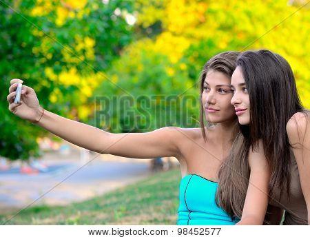 Two girls taking their snapshot in park