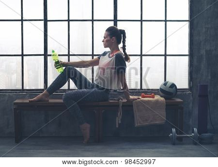 Fit Woman Sitting On Bench In Loft Gym Holding Water Bottle