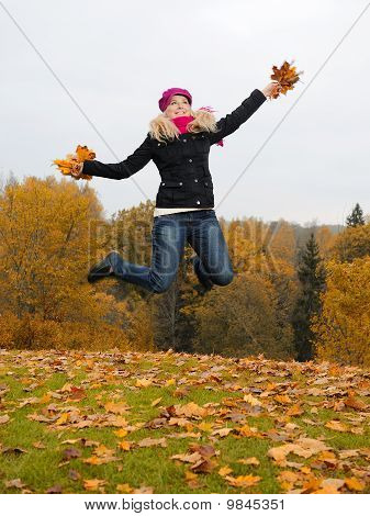 Beautiful Girl With Autumn Leafs In A Park Jumping And Smiling
