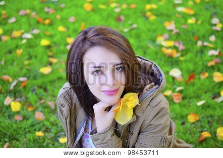 Beautiful young woman holding autumn leaves and sitting ot grass.