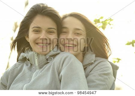 Two beautiful young women hugging and laughing outside