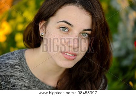 Summer portrait of a beautiful freckled young woman with colorful background