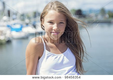 Young long-haired teen girl standing on the beach