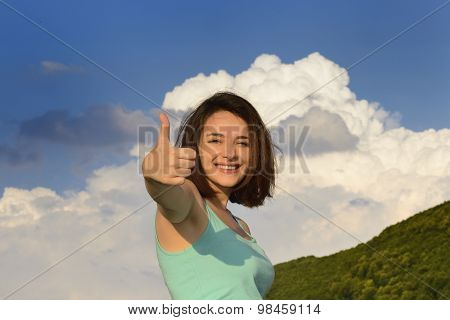 Beautiful young woman giving thumbs up sign in front of cloudy sky and smiling.