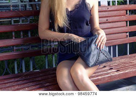 Fashionable stylish young woman open black handbag