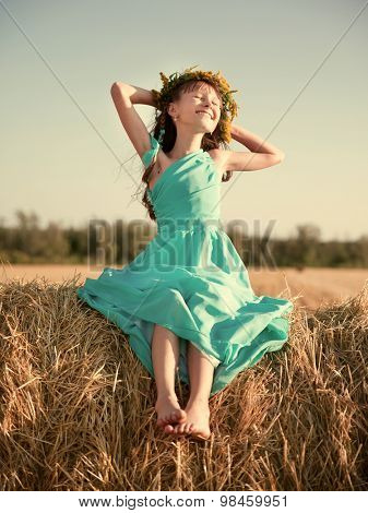 little girl sitting on a haystack