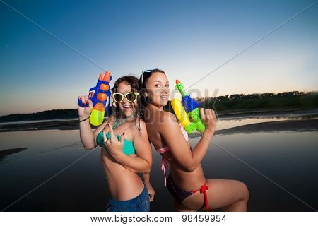 Two young girl posing with water pistols