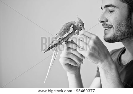 Attractive man playing with his parrot indoors. Black and white photograph