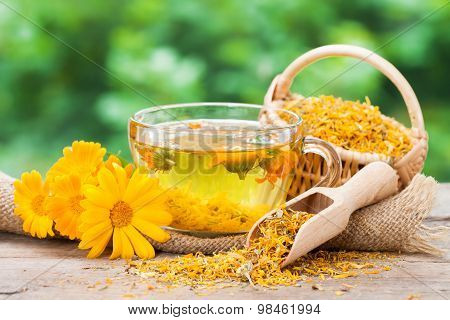 Cup Of Healthy Marigold Tea And Calendula Flowers.