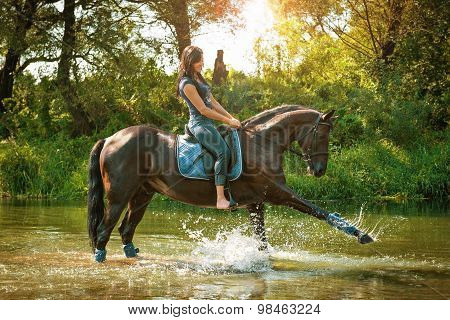 Woman on horseback rides along the river on a hot summer day.