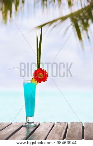 Blue Lagoon Cocktail On The Table At Tropical Beach