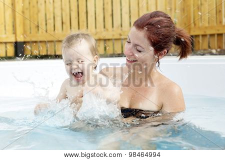 Portrait of young family with baby and toddler in swimming pool