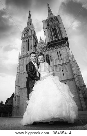 Newlyweds Holding Hands In Front Of Cathedral Black And White