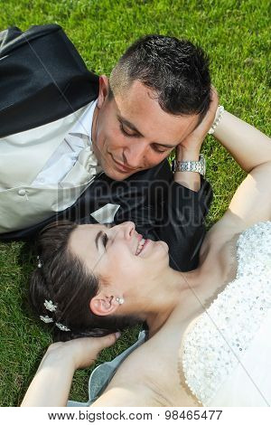 Newlyweds On Grass Looking At Each Other