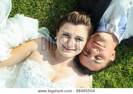 Newlyweds Posing On Grass