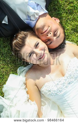 Married Couple Lying On Grass