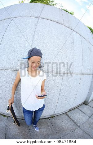 young skateboard use cellphone rest leaning on wall