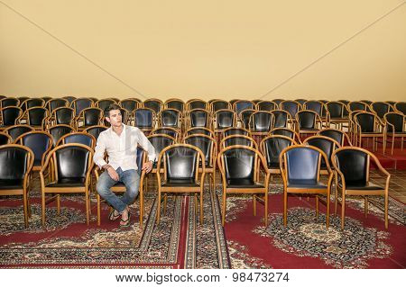 Handsome Man Sitting at the Audience Chair Alone