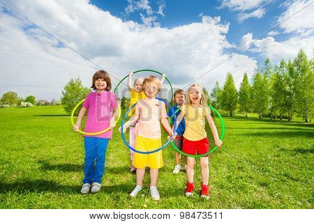 Kids hold hula hoops during exercising activity