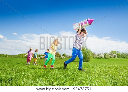 Boy runs with rocket toy and kids chasing after